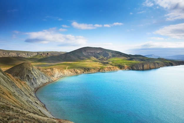 Seehafen mit blauem wasser, grünem feld und blauem himmel mit wolken