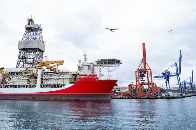 Seehafen mit festgemachtem frachtschiff bei bewölktem wetter mit fliegenden möwen in istanbul, türkei