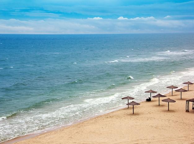 Seeküste mit mit stroh gedeckten regenschirmen