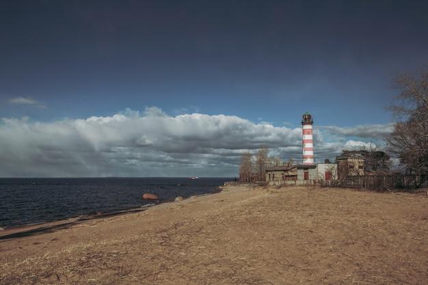 Seeküste mit rot-weißem leuchtturm.
