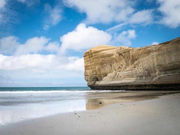 Seelandschaft mit blauem himmel und sandsteinfelsen als hauptthema tunnelstrand neuseeland