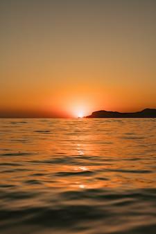 Seelandschaft mit klarem himmel und wellen auf sonnenuntergang
