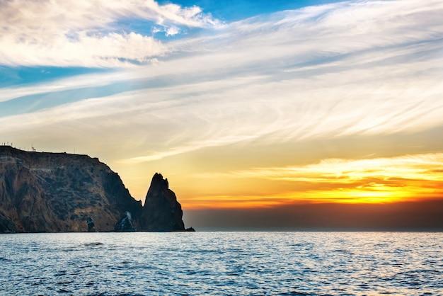 Seelandschaft mit sonnenuntergang über felsen und dramatischem himmel