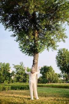 Seele üben. rückansicht einer blonden frau in hose und bluse, die die arme vor einem hohen grünen baum im park hebt