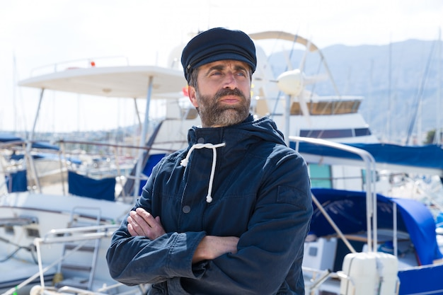 Seemann im jachthafenhafen mit bootshintergrund