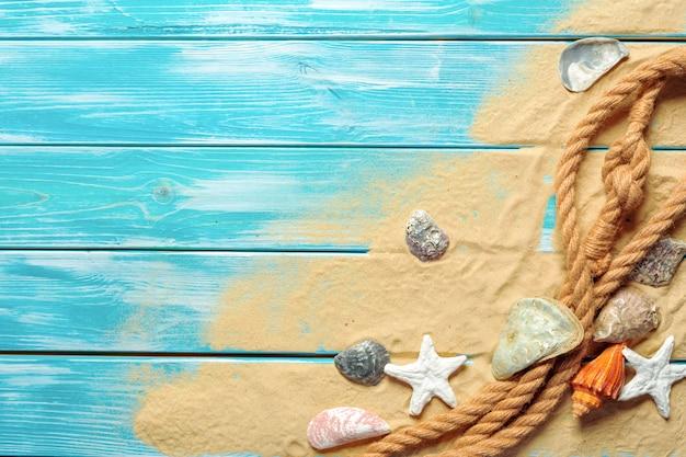 Seeseil mit vielen verschiedenen seeoberteilen auf dem meersand auf einem blauen hölzernen. ansicht von oben