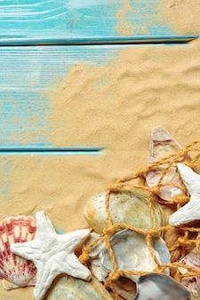 Seeseil mit vielen verschiedenen seeoberteilen auf dem meersand auf einem blauen hölzernen hintergrund. ansicht von oben