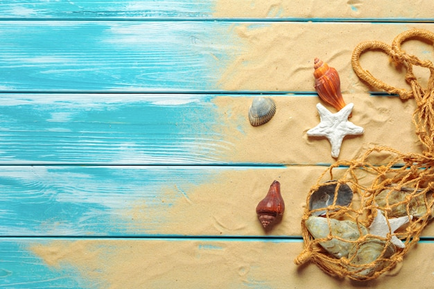 Seeseil mit vielen verschiedenen seeoberteilen auf dem meersand auf einem blauen hölzernen hintergrund