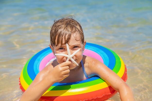 Seestern am strand in den händen eines kindes