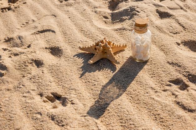 Seestern und glas mit muscheln am sandstrand