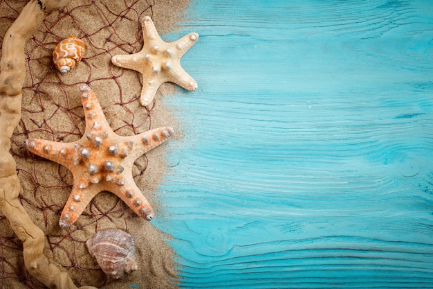 Seesterne, kieselsteine und muscheln, die auf einem blauen hölzernen hintergrund liegen. es gibt einen platz für etiketten.