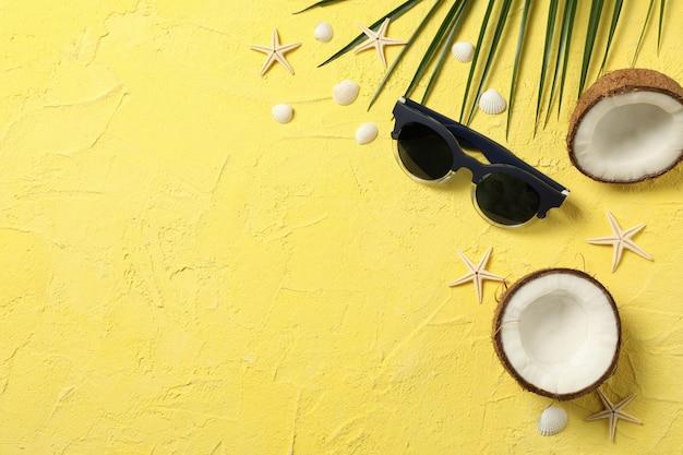 Seesterne, kokosnuss, palmzweig und sonnenbrille auf gelb, platz für text