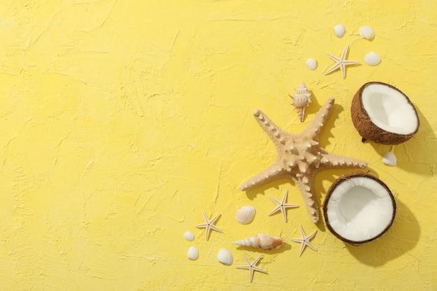 Seesterne, kokosnuss und muscheln auf gelb, platz für text