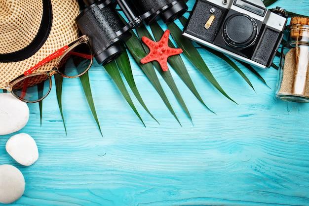 Seesterne, seesteine, palmblätter und muscheln, die auf einem blauen hölzernen hintergrund liegen. es gibt einen platz für etiketten.