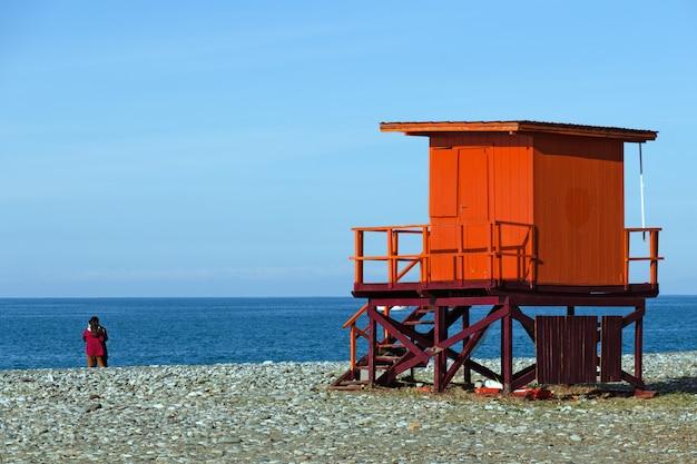 Seestrand mit leibwächterturm und ein paar in der nähe des wassers.
