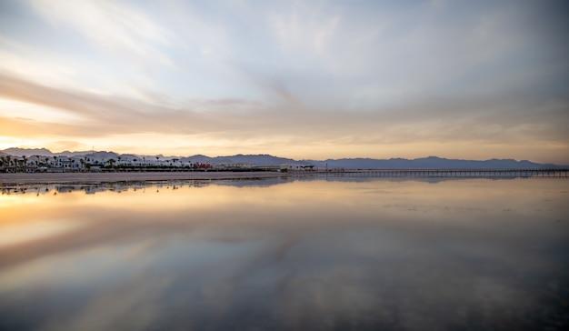 Seestück mit einem reflektierenden himmel. die sonne geht über der stadt in der nähe der berge unter.