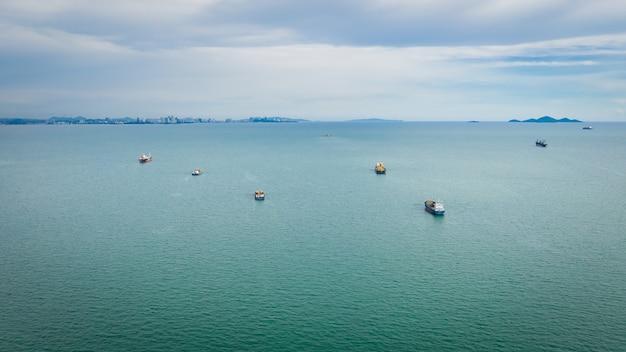 Seestückcontainer-frachtschiffimport und -export mit wolkenhimmelvogelperspektive