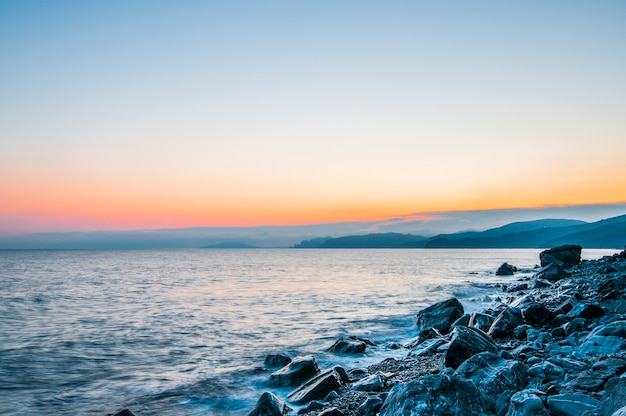 Seeufer und felsiger strand, blauer himmel mit weißen wolken, bergen und kleinem dorf