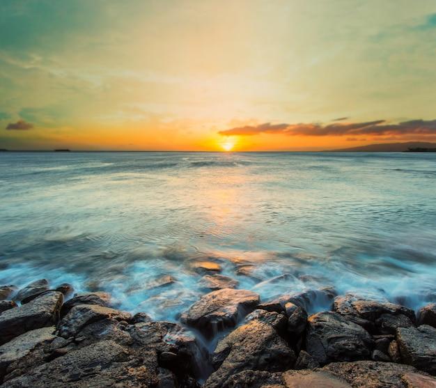 Seewelle schlug den felsen bei sonnenuntergang in hawaii