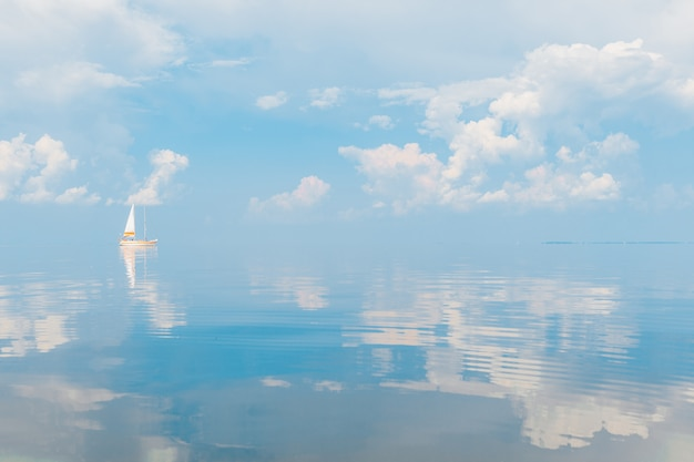 Segelboot im meer am sonnigen tag auf malerischem meerblick der fabelhaften märchen mit wolken reflektierte sich im wasser.