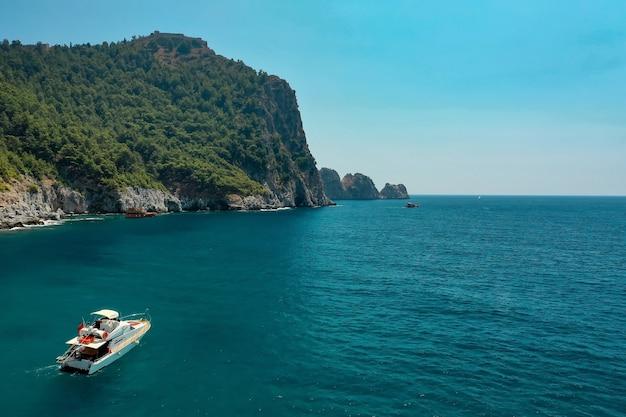 Segelboot im meer im abendsonnenlicht über schönen großen bergen, luxuriöses sommerabenteuer, aktiver urlaub im mittelmeer, türkei