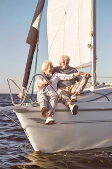 Segeln macht spaß, ein glückliches seniorenpaar, das auf einem ruhigen blauen seemann an der seite eines segelbootes sitzt