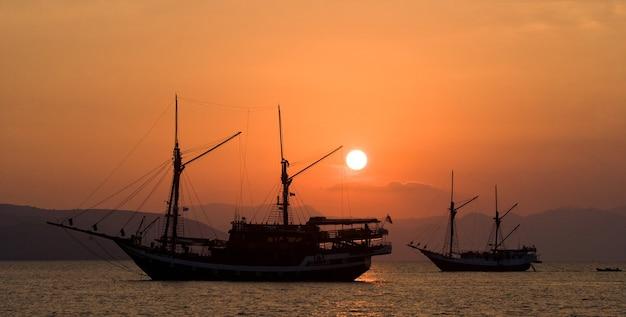 Segelschiff auf dem meer bei sonnenaufgang (sonnenuntergang). indonesien. asien.