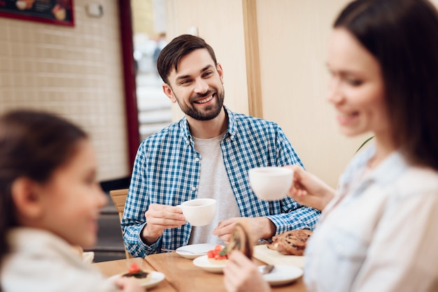 Segen-glückliche familie, die kuchen in der cafeteria isst.