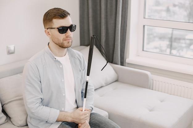 Sehbehinderter mann, der mit stock auf der couch sitzt