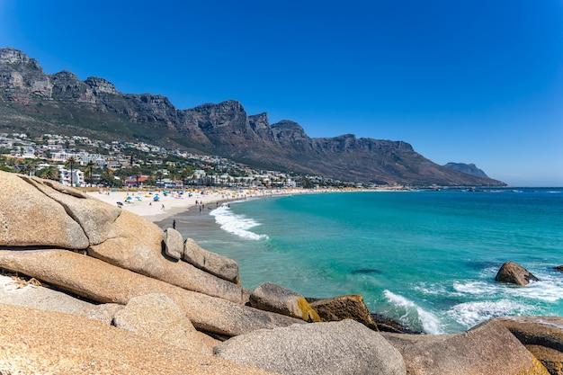 Sehen sie camps bucht schönen strand mit türkisfarbenem wasser und bergen in kapstadt, südafrika