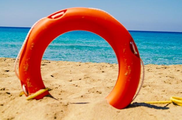 Sehen sie landschaft durch orange leben bouy saver ring im sand am strand