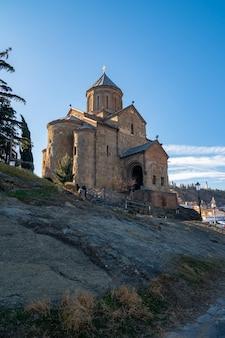 Sehen sie sich die metekhi-kirche am morgen über dem fluss kura in tiflis, georgien, an