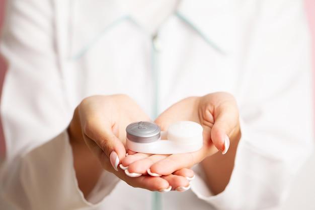 Sehprobleme, nahaufnahme der frau, die behälter mit kontaktlinsen hält