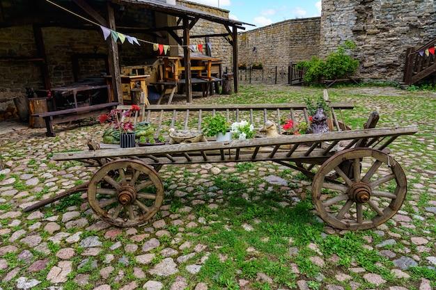 Sehr alt aussehende kutsche mit verschiedenen dekorationen auf einer sehr alten gepflasterten straße.