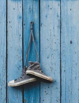 Sehr alte textilturnschuhe, die an einem nagel hängen