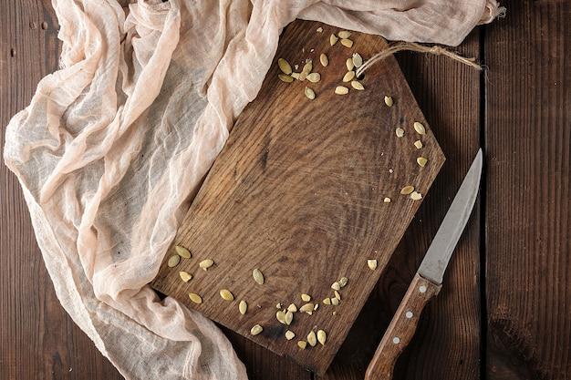 Sehr altes leeres braunes hölzernes schneidebrett und küchenserviette