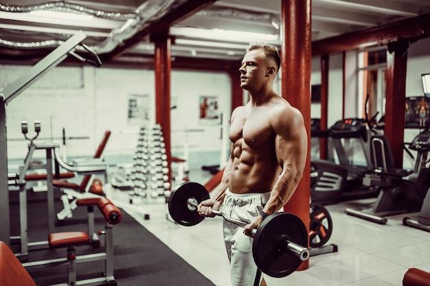Sehr athletischer typ bodybuilder der energie, führen übung mit dummköpfen durch