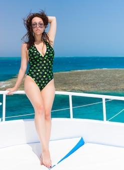 Sehr attraktive frau, die an einem sonnigen sommertag auf der yacht steht, brise haare entwickeln, schönes türkisfarbenes meer im hintergrund