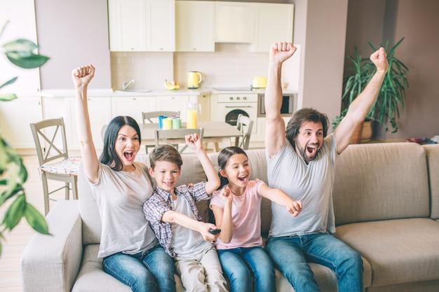 Sehr aufgeregte und glückliche familie jubeln. sie halten ihre hände hoch. die leute schreien und schreien. sie freuen sich.