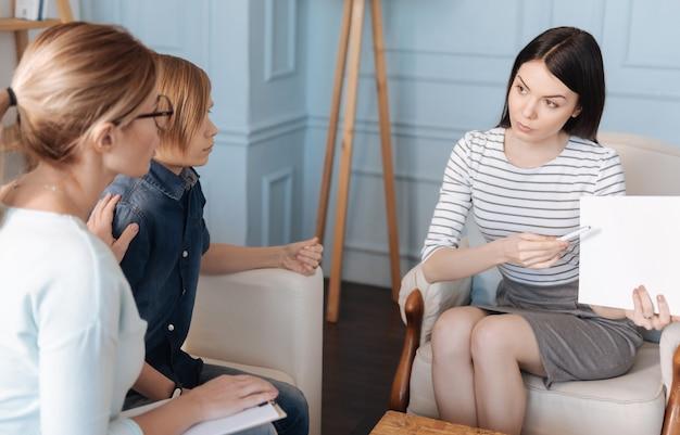 Sehr aufmerksamer junge, der jeans kostüm hält, das linke hand auf weißem rücken des sofas hält, während er gerade auf papier schaut