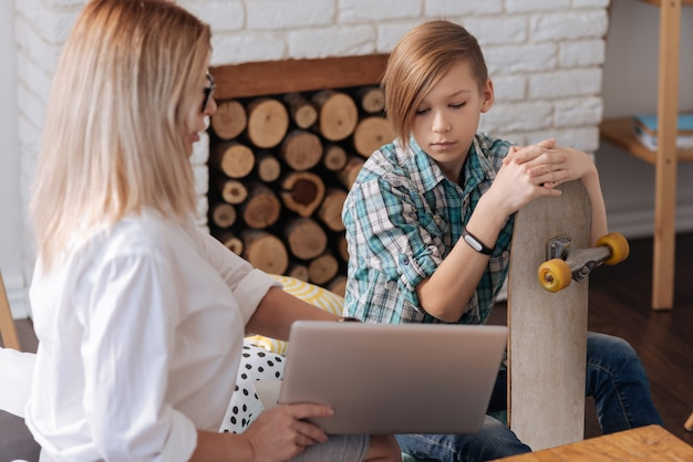 Sehr aufmerksamer teenager, der fitnessarmband auf der rechten hand trägt, die gegenüber frau sitzt, während sie nach unten schaut