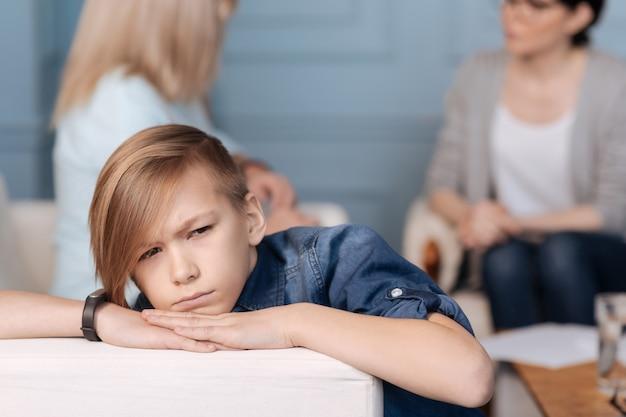 Sehr aufmerksamer teenager, der jeans kostüm hält händchen haltend auf weißem rücken des sofas, während kinn darauf setzt