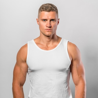 Sehr fit mann posiert beim tragen von tanktop