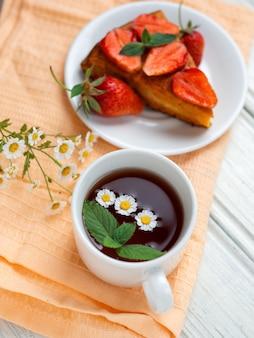 Sehr geschmackvoller karottenkuchen verziert mit erdbeeren auf einer weißen tabelle und einer schale wohlriechendem blumentee