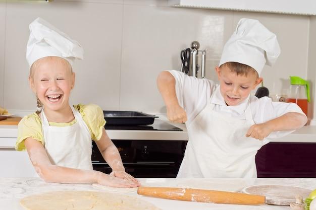 Sehr glückliche junge köche, die essen in der küche zubereiten.