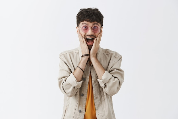 Sehr glücklicher hübscher kerl, der mit sonnenbrille gegen die weiße wand aufwirft