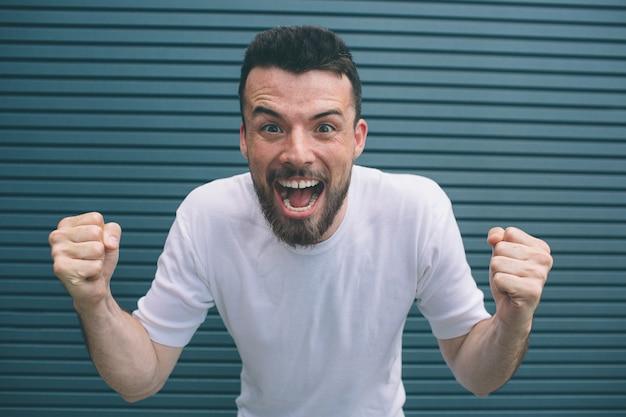 Sehr glücklicher mann steht und schaut in die kamera. er hält hände in fäusten und öffnet den mund sehr weit. isoliert auf gestreift
