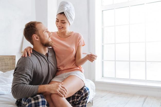 Sehr glückliches paar, das morgenzeit zusammen verbringt, während frau auf schoß ihres mannes sitzt und einen schwangerschaftstest zeigt