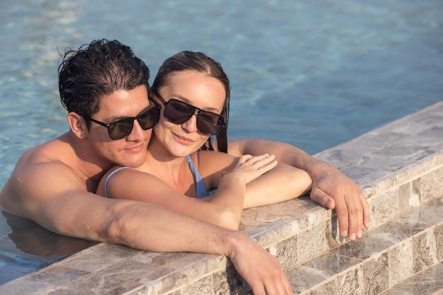 Sehr glückliches paar mit sonnenbrille genießen sich im schwimmbad. mann, der frau auf händen hält