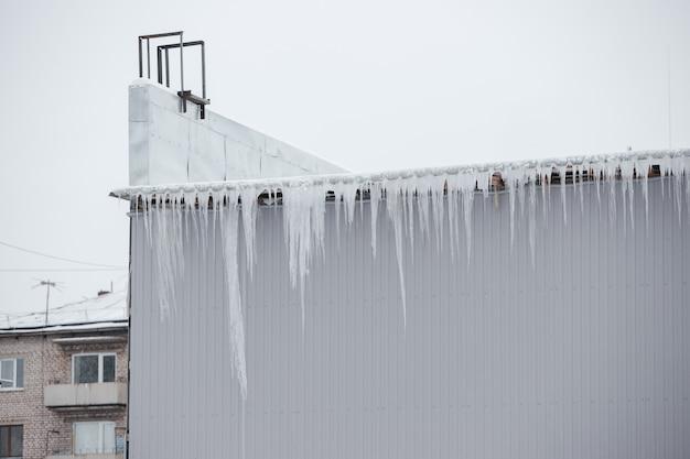 Sehr große eiszapfen hängen vom dach.